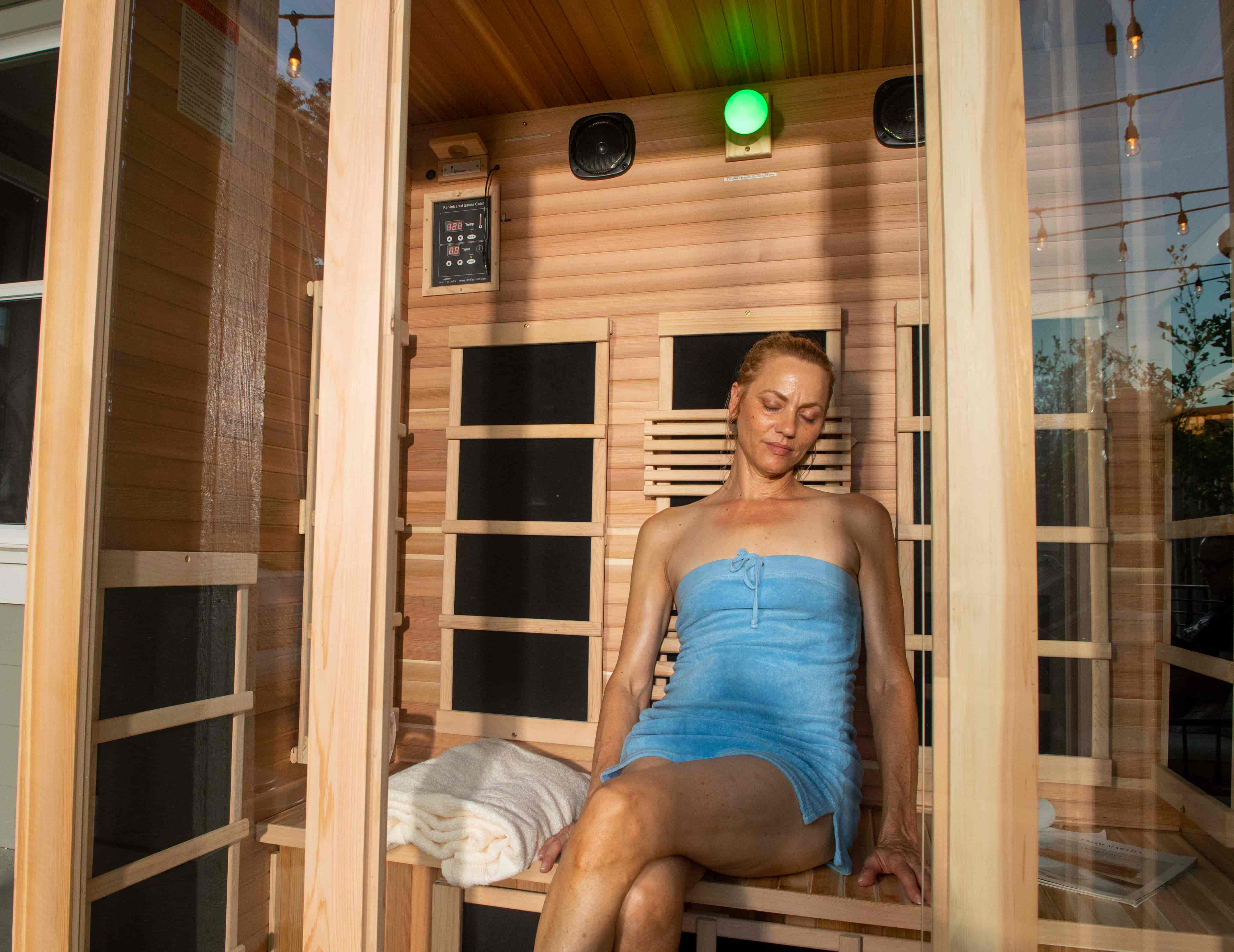 woman using an infrared sauna the freedom 3 person far infrared sauna by jnh lifestyles